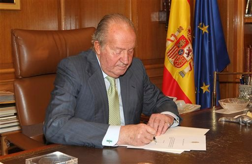 In this photo released by the Royal Palace on Monday, June 2, 2014, Spain's King Juan Carlos signs a document in the Zarzuela Palace opening the way for his abdication.