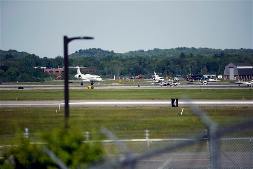 The site of a plane crash is seen in the distance, across Hanscom Field in Bedford, Mass., Sunday, June 1, 2014.