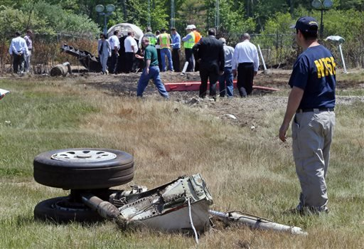 A National Transportation Safety Board official stands beside a piece of the landing gear at the scene Monday, June 2, 2014, in Bedford, Mass., where a plane plunged down an embankment and erupted in flames during a takeoff attempt at Hanscom Field. (AP)