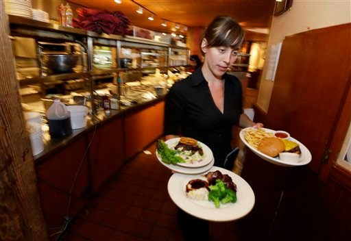 In this June 2, 2014 photo, Wendy Harrison, a waitress at the icon Grill in Seattle, carries food to a table as she works during lunchtime. (AP)