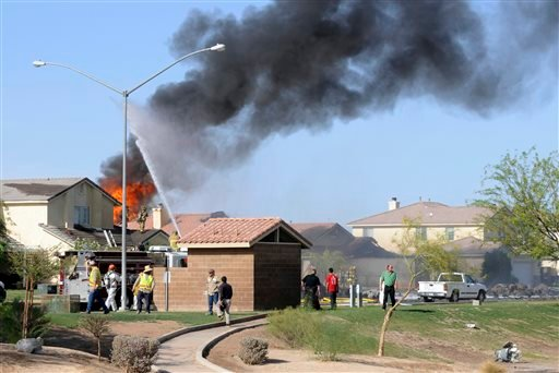 Smoke and flames rise after a Marine jet crashed into a residential area in the desert community of Imperial, Calif., setting two homes on fire Wednesday, June 4, 2014.