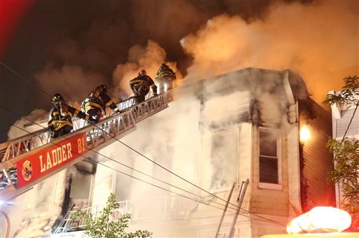 Firefighters battle a fire that tore through three townhouses on New York City's Staten Island early Thursday, June 5, 2014. (AP)