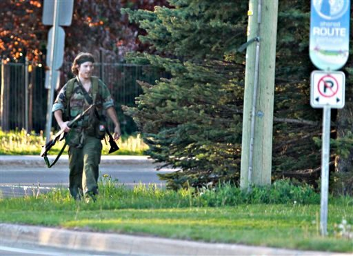 A heavily armed man that police have identified as Justin Bourque walks on Hildegard Drive in Moncton, New Brunswick, on Wednesday, June 4, 2014, after several shots were fired in the area. (AP)