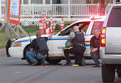 Police officers take cover behind their vehicles in Moncton, New Brunswick, on Wednesday June 4, 2014. (AP)