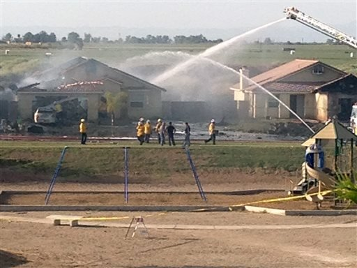 This photo provided by Isaac Ramos shows firefighters putting out a fire caused when a military jet crashed in residential neighborhood in Imperial, Calif., Wednesday, June 4, 2014. Witnesses say two houses caught fire after the crash. (AP Photo)