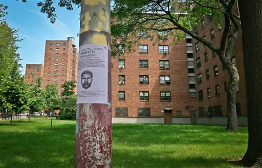 A reward poster, posted at the Boulevard Houses, shows a police sketch of a man wanted for murder, Wednesday, June 4, 2014, in the Brooklyn borough of New York. (AP)