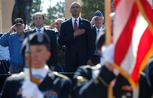 U.S. President Barack Obama, centre and French President Francois Hollande stand, during the playing of the Star Spangled Banner, at Normandy American Cemetery at Omaha Beach as he participates in the 70th anniversary of D-Day in Colleville sur Mer.