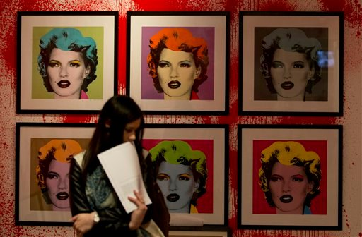 A member of the media stands by art work of British model Kate Moss, by British artist Banksy, during a press preview of an unauthorised retrospective exhibition showing some 70 works of art, in London, Friday, June, 6, 2014.