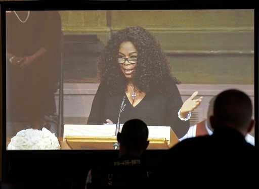 Media members watch a screen as Oprah Winfrey speaks during a memorial service for poet and author Maya Angelou at Wait Chapel. at Wake Forest University in Winston-Salem, N.C., Saturday, June 7, 2014.