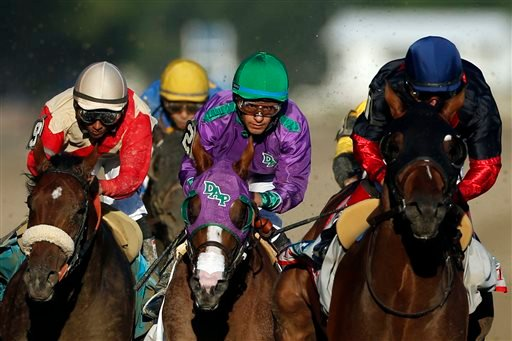 California Chrome, center, is flanked by Wicked Strong, left, and Tonalist, right, as they run down the backstretch during the 146th running of the Belmont Stakes horse race at Belmont Park, Saturday, June 7, 2014, in Elmont, N.Y.