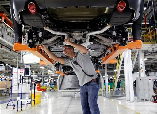 In this May 8, 2013 file photo, Jeff Caldwell, 29, a chassis assembly line supervisor, checks a vehicle on the assembly line at the Chrysler Jefferson North Assembly plant in Detroit.