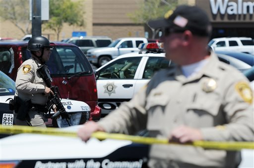 Las Vegas police officers are near the scene of a shooting in Las Vegas, Sunday, June 8, 2014.