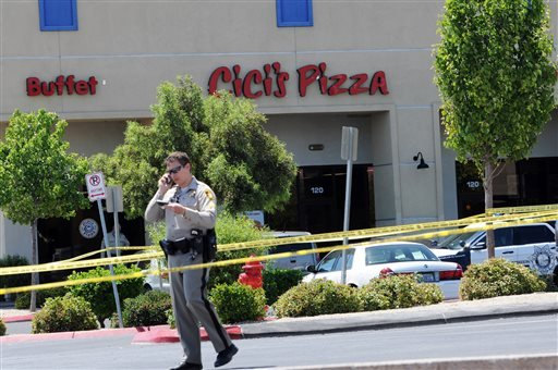 A Las Vegas police officer walks near the scene of a shooting in Las Vegas, Sunday, June 8, 2014.