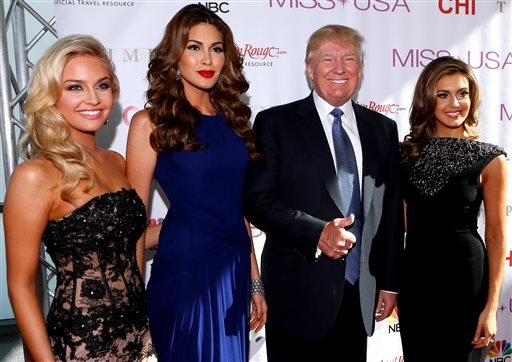 From left, Miss Teen USA 2013 Cassidy Wolf, Miss Universe 2013 Gabriela Isler, Donald Trump, and Miss USA 2013 Erin Brady pose during a red carpet event before the Miss USA 2014 pageant in Baton Rouge, La., Sunday, June 8, 2014.