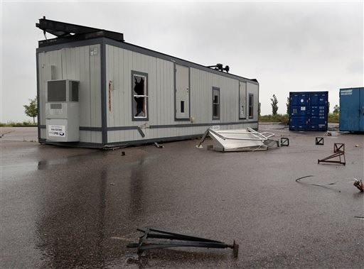 A damaged office trailer is flipped over after if was blown over by a reported tornado at the Blackstone County Club in southeast Aurora, Colo., on Sunday, June 8, 2014.