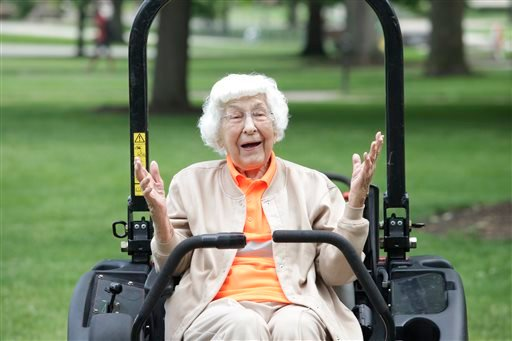 Trudy Price, who turned 100 on Monday, reacts while sitting on a riding lawn mower, Monday, June 9, 2014, on the campus of Bowling Green State University in Bowling Green, Ohio. (AP)