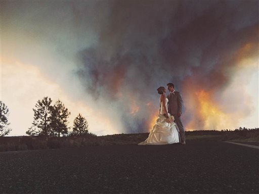 In this Saturday, June 7, 2014 photo provided by Josh Newton, newlyweds Michael Wolber and April Hartley pose for a picture near Bend, Ore., as a wildfire burns in the background.