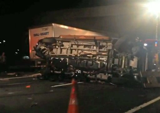 In this image from video the limousine bus carrying Tracy Morgan and six other people lies on it's side early Saturday morning, June 7, 2014, on the New Jersey Turnpike.