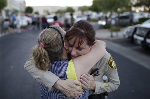 Cheri Rasmussen, left, embraces Las Vegas Metropolitan Police Lt. Roxanne McDaris after a vigil near CiCi's Pizza Monday, June 9, 2014 in Las Vegas.