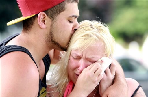 Two people comfort each other as they await word about the safety of students after a shooting at Reynolds High School Tuesday, June 10, 2014, in Troutdale, Ore.