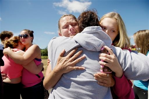 Brandi Wilson, left, and her daughter, Trisha Wilson, 15 embrace Trish Hall, a mother waiting for her student, as students arrived at the Fred Meyer grocery store in Wood Village, Ore. after a shooting at Reynolds HS June 10, 2014.(AP Photo/Troy Wayrynen)