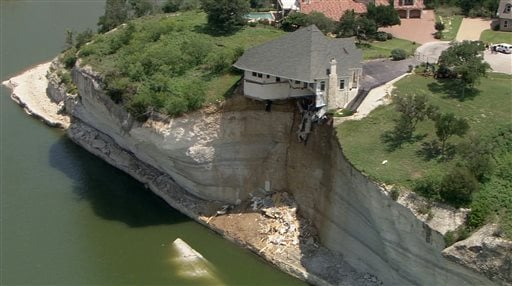 In this image taken from video provided June 12, 2014, by WFAA.Com, a luxury house teeters on a cliff about 75 feet above Lake Whitney in Whitney, Texas. (AP)