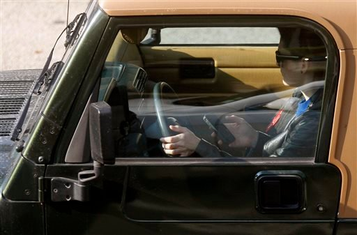 In this Dec. 14, 2011, file photo, a driver uses an iPhone while driving in Los Angeles.