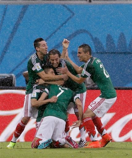 Mexico's Oribe Peralta celebrates with teammates after scoring the opening goal during the group A World Cup soccer match between Mexico and Cameroon in the Arena das Dunas in Natal, Brazil, Friday, June 13, 2014. (AP Photo/Ricardo Mazalan)