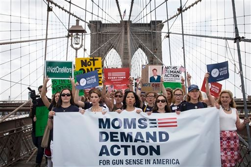 Hundreds of demonstrators march across the Brooklyn Bridge to call for tougher gun control laws, Saturday, June 14, 2014, in New York.