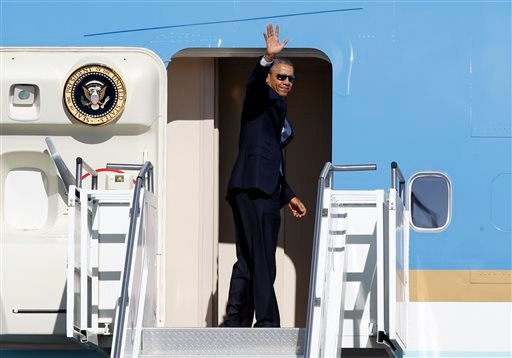 President Barack Obama waves in the direction of members of the media as he boards Air Force One at Palm Springs International Airport, Saturday, June 14, 2014, in Palm Springs, Calif.
