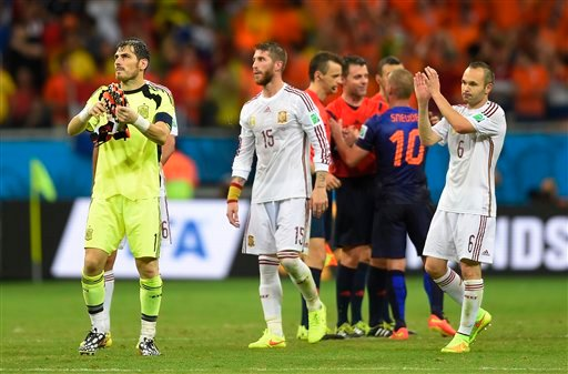 Spain's goalkeeper Iker Casillas, left, Spain's Sergio Ramos, centre and Spain's Andres Iniesta react after the group B World Cup soccer match between Spain and the Netherlands at the Arena Ponte Nova in Salvador, Brazil, Friday, June 13, 2014.