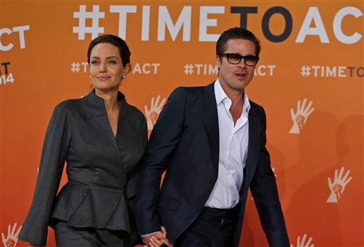 Angelina Jolie, left, special envoy of the United Nations High Commissioner for Refugees, and her partner Brad Pitt arrive at the 'End Sexual Violence in Conflict' summit in London, Friday, June 13, 2014.