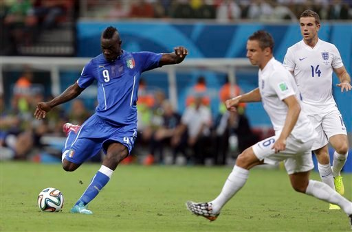 Italy's Mario Balotelli, left, gets in a shot as England's Phil Jagielka, center, and Jordan Henderson, right, defend during the group D World Cup soccer match between England and Italy at the Arena da Amazonia in Manaus, Brazil, Saturday, June 14, 2014.