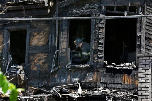 Firefighters pick through the rubble of a burned out home as they look for clues to a fire that authorities say killed six people in Newark, N.J., Sunday, June 15, 2014.
