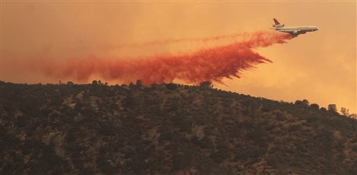 This jet powered DC-10 air tanker #910 makes a long drop of fire retardant on the Shirley Fire, Saturday, June 14, 2014 in the Alta Sierra area where the wildfire has consumed more than 800 acres. (AP Photo/The Bakersfield Californian, Casey Christie)