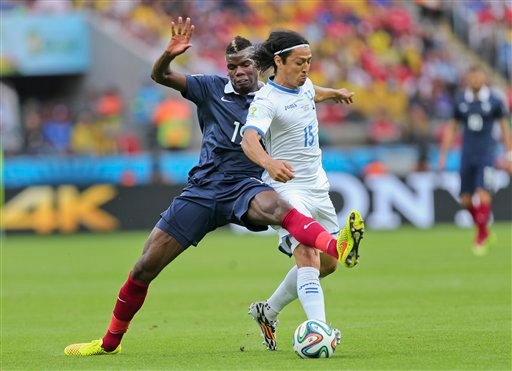 France's Paul Pogba, left, challenges Honduras' Roger Espinoza during the group E World Cup soccer match between France and Honduras at the Estadio Beira-Rio in Porto Alegre, Brazil, Sunday, June 15, 2014. (AP Photo/David Vincent)