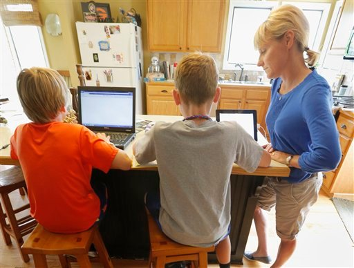 In this photo taken Saturday, June 7, 2014, Megan King works with her sons Joshua, 9, left, and Benjamin, 11, center, in her home in Lawrence, Kan.