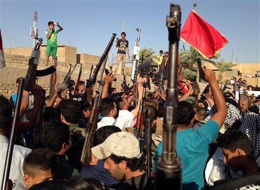 Shiite tribal fighters raise their weapons and chant slogans against the al-Qaida-inspired Islamic State of Iraq and the Levant (ISIL) in the east Baghdad neighborhood of Kamaliya, Iraq, Sunday, June 15, 2014.