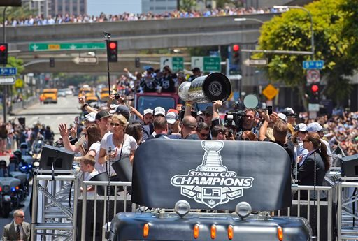 Los Angeles Kings' Anze Kopitar, center, holds up the NHL hockey Stanley Cup trophy while riding in a parade through downtown Los Angeles, Monday, June 16, 2014.