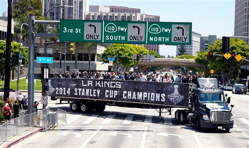Members of the Los Angeles Kings NHL hockey team ride on the back on a semi truck in a parade through downtown Los Angeles, Monday, June 16, 2014.