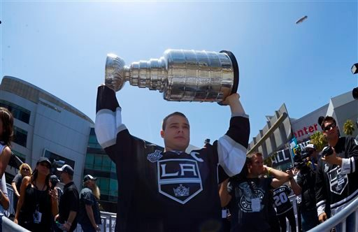 Los Angeles Kings right wing Dustin Brown holds up the NHL hockey Stanley Cup trophy while riding in a parade, Monday, June 16, 2014, in Los Angeles.