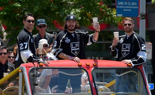 Los Angeles Kings defensemen Alec Martinez, from left, Drew Doughty and center Trevor Lewis pose after riding in a parade, Monday, June 16, 2014, in Los Angeles.
