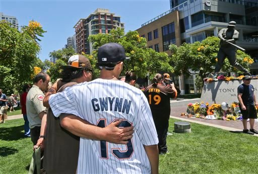 """Two mourner console each other at the Tony Gwynn """"Mr. Padre"""" statue outside Petco Park, Monday, June 16, 2014, in San Diego."""
