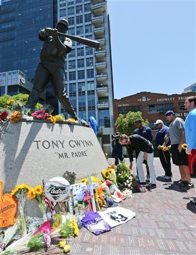 """A.G. Spanos, CEO of the San Diego Chargers, leads his team as they place flowers and other mementos at the base of the Tony Gwynn """"Mr. Padre"""" statue, Monday, June 16, 2014, in San Diego."""