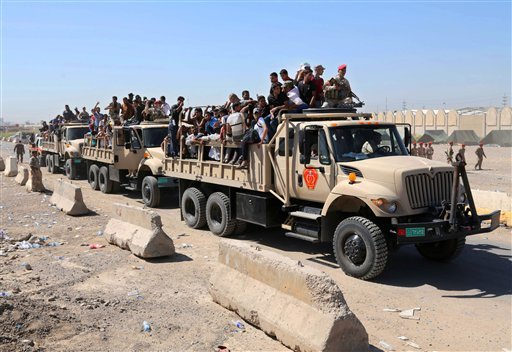 Iraqi men fill military trucks to join the Iraqi army at the main recruiting center in Baghdad, Iraq, Tuesday, June 17, 2014, after authorities urged Iraqis to help battle insurgents.