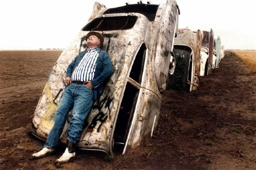 FILE - In this June 1984 file photo, Stanley Marsh 3 leans on one of the 10 Cadillacs buried down on his ranch west of Amarillo, Texas, along old Route 66. (AP)