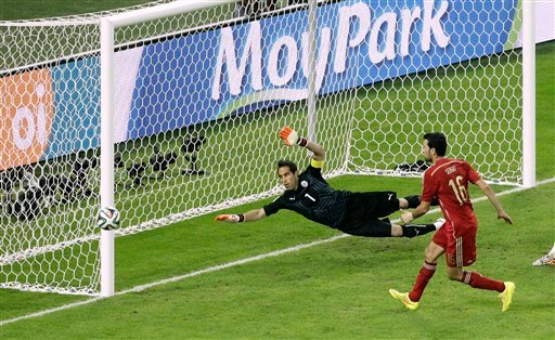 Spain's Sergio Busquets, right, shoots past the goal of Chile's goalkeeper Claudio Bravo during the group B World Cup soccer match between Spain and Chile at the Maracana Stadium in Rio de Janeiro, Brazil
