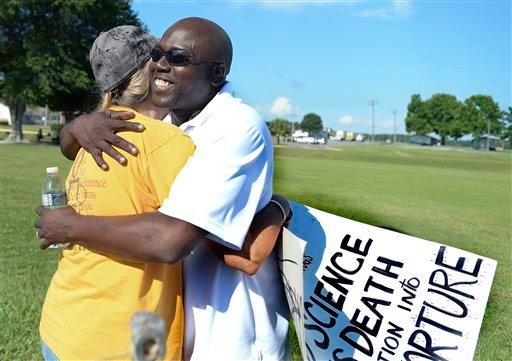 Herman Lindsey, right, hugs a colleague in front of the Florida State Prison near Starke, Fla. Wednesday, June 18, 2014. (AP Photo/Phil Sandlin)
