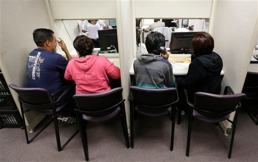 FILE - This Mach 31, 2014 file photo shows people using a a phone bank to sign up for health care insurance at the business office of Parkland Hospital in Dallas. (AP)