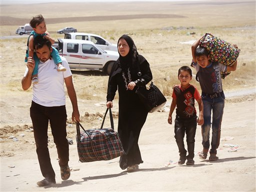 Iraqis who have fled the violence in their hometown of Mosul line arrive at Khazir refugee camp outside of Irbil, 217 miles (350 kilometers) north of Baghdad, Iraq, Monday, June 16, 2014.